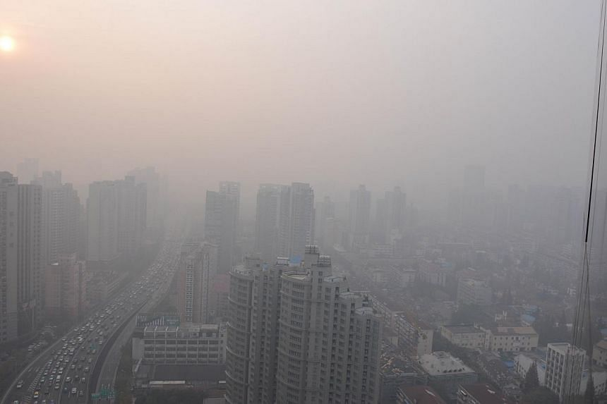 This picture taken on Dec 5, 2013, shows traffic (left) in downtown Shanghai during a period of severe pollution. -- FILE PHOTO: AFP