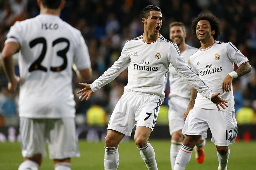 Real Madrid's Cristiano Ronaldo (second from left) celebrates his second goal against Osasuna with teammates during their La Liga match at Santiago Bernabeu stadium in Madrid on April 26, 2014. -- PHOTO: AFP
