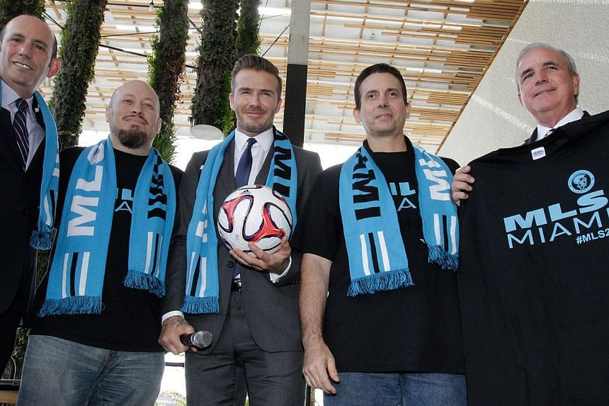 This photo taken on Feb 5, 2014 shows former football star David Beckham (centre), wearing a Major League Soccer (MLS) scarf, posing with MLS fans and MLS Commissioner Don Garber (left) and Miami-Dade County Mayor, Carlos A. Gimenez (right), after ho