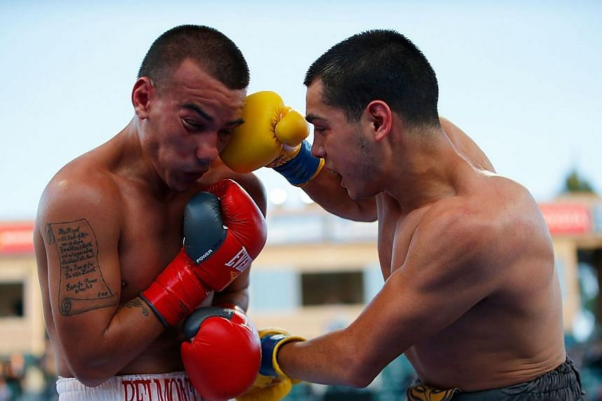 Omar Figueroa Jr punches Jerry Belmontes during their WBC Lightweight World Championship title bout at StubHub Center on April 26, 2014 in Los Angeles, California. -- PHOTO: AFP