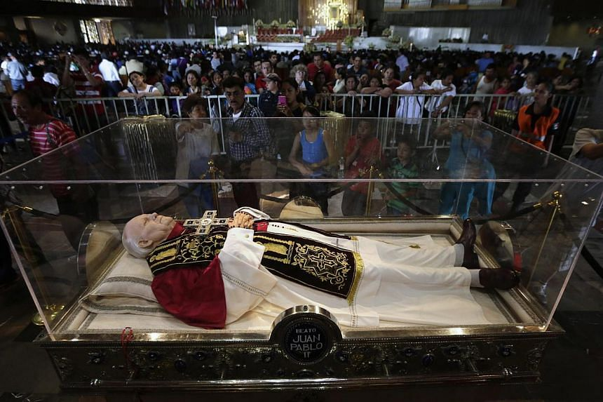 The faithful look at a glass coffin containing a wax figure of Pope John Paul II at the Basilica of Guadalupe in Mexico City on April 26, 2014. -- PHOTO: REUTERS