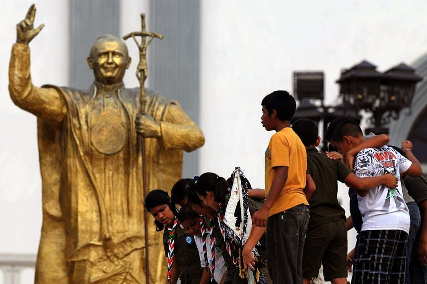 A group of scouts walk in front of a statue of the late Pope John Paul II in Tegucigalpa, Honduras, on April 26, 2014, on the eve of the canonisation of Pope John Paul II and Pope John XXIII. -- PHOTO: AFP