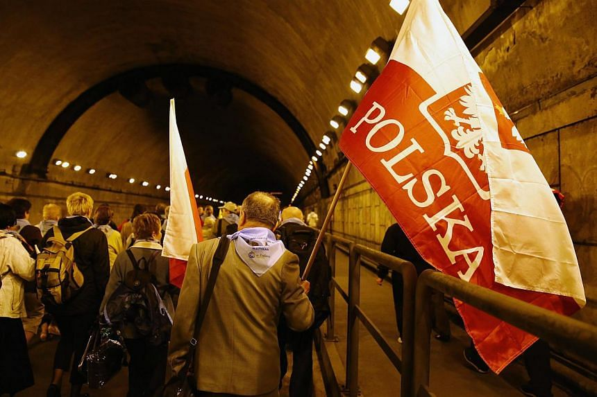 Polish pilgrims walk with a flag through a tunnel as they arrived for the canonisation ceremonies of Pope John XXIII and Pope John Paul II at the Vatican, in Rome on April 27, 2014. -- PHOTO: REUTERS