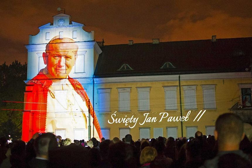 An image of Pope John Paul II is projected during a multimedia show a night before his canonisation, in Krakow, Poland, on April 26, 2014. -- PHOTO: REUTERS