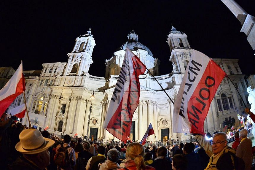 Pilgrims holding Polish flags gather outside Sant'Agnese in Agone church at Piazza Navona on April 26, 2014 in Rome during a vigil on the eve of the canonisation of late Pope John Paul II and John XXIII. -- PHOTO: AFP