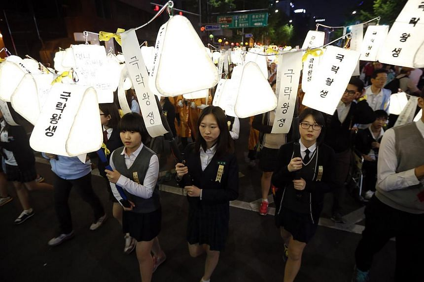 Students holding lanterns bearing messages for the victims of the capsized passenger ship Sewol march during a lotus lantern parade to celebrate the upcoming birthday of Buddha and to commemorate the victims in Seoul on April 26, 2014. -- PHOTO: REUT