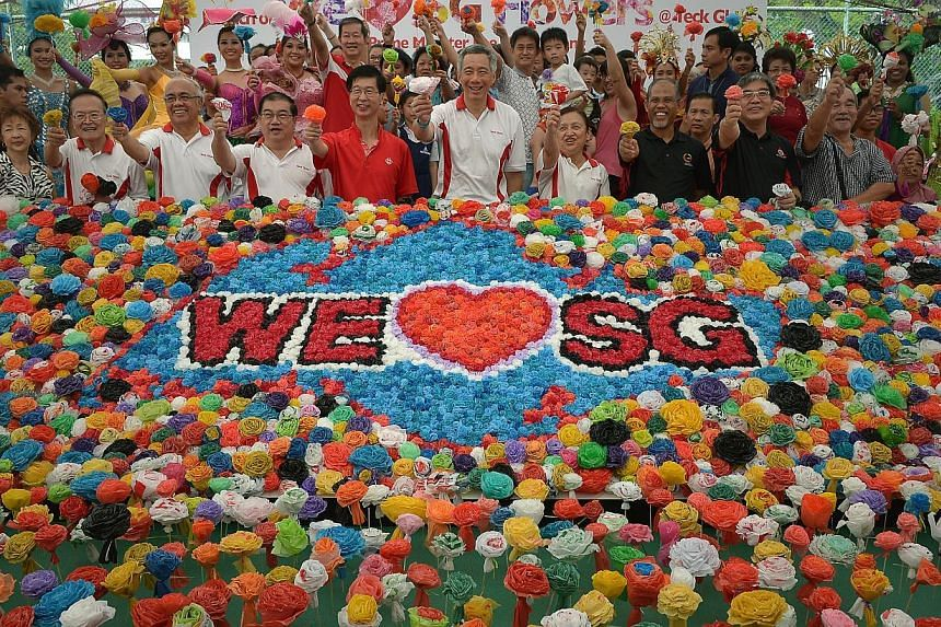 """Prime Minister Lee Hsien Loong (centre) posing for pictures with Teck Ghee residents and volunteers from 87 GRC divisions and constituencies at Teck Ghee Community Club, where an initiative to craft one million""""We love SG flowers"""" from used bag"""
