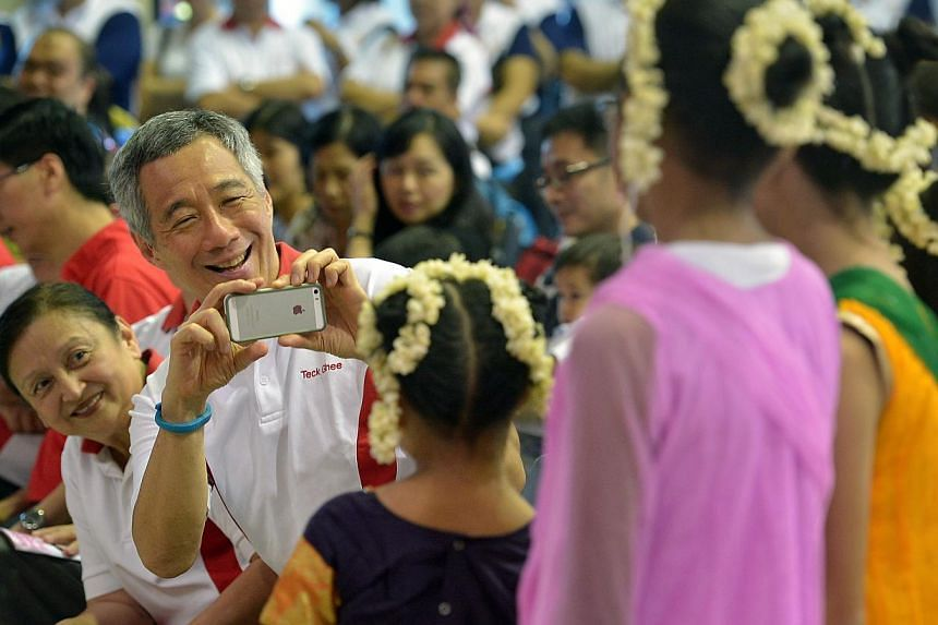 Prime Minister Lee Hsien Loong taking a picture of children with his handphone after their performance at the Teck Ghee Baby Show held at Teck GheeCommunity Club on April 27, 2014. -- ST PHOTO: KUA CHEE SIONG