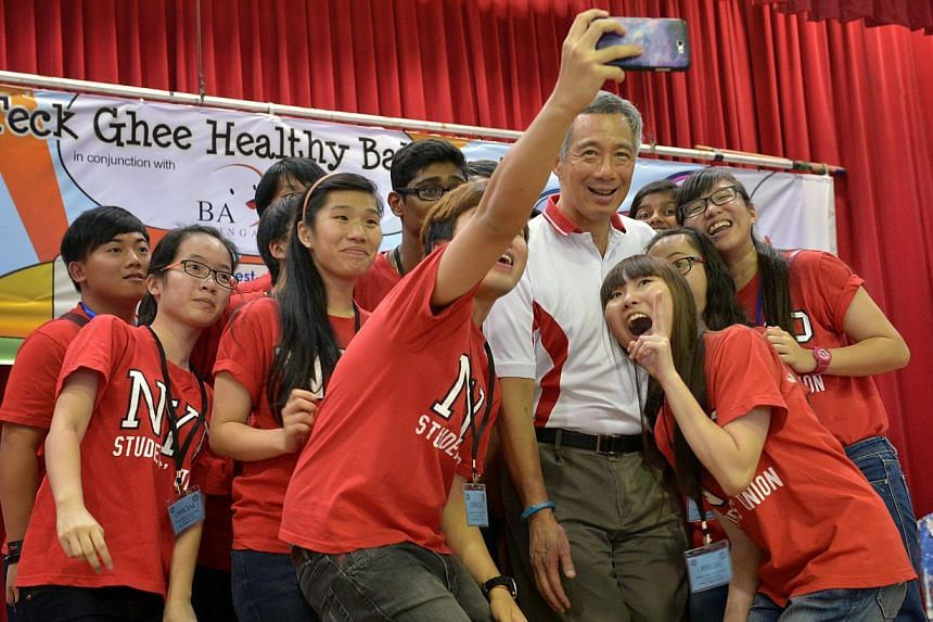 """Student Union members from Nanyang Polytechnic taking a """"selfie"""" with Prime Minister Lee Hsien Loong at the Teck Ghee Baby Show held at Teck Ghee Community Club on April 27, 2014. -- ST PHOTO: KUA CHEE SIONG"""