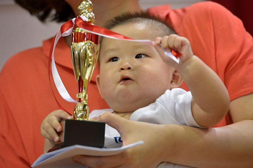 Tyler Li, who is seven months old, playing with the ribbons on the trophy after coming in fifth at the Healthy Baby contest at the Teck Ghee Baby Show on April 27, 2014. -- ST PHOTO: KUA CHEE SIONG