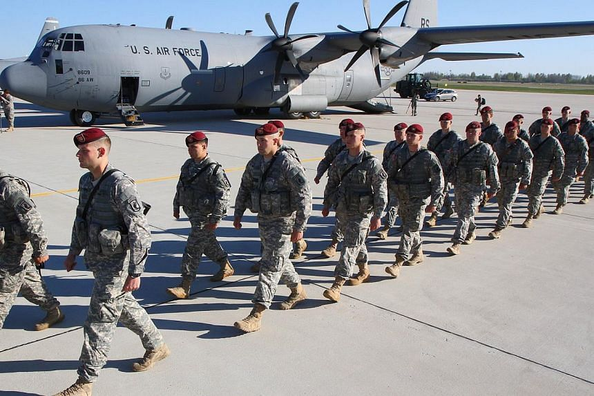 US soldiers walk at the airport after arriving at the air force base near Siauliai Zuokniai, Lithuania, on April 26, 2014. The Philippines and the United States will sign a new defence pact on Monday morning giving more US troops, warships and p