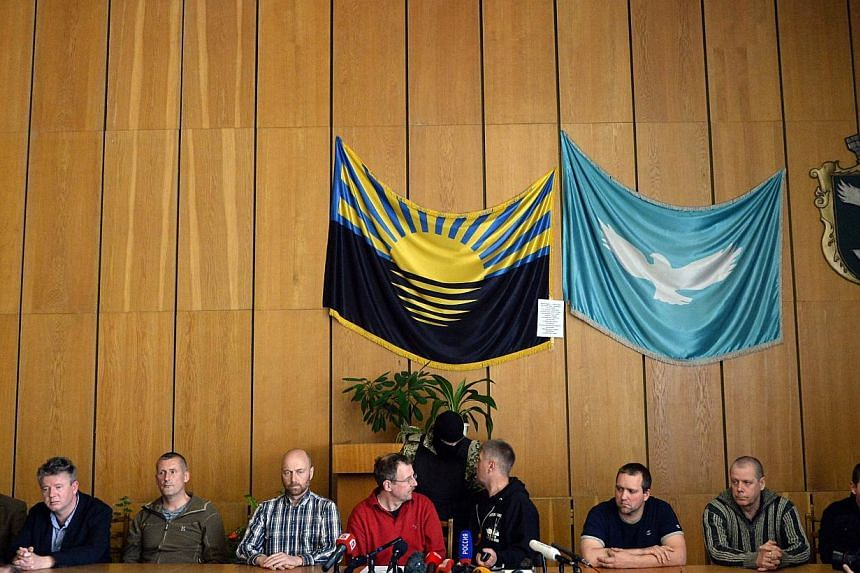 """Eight detained OSCE observers take part in a press conference of the pro-Russian separatist leader and self-proclaimed """"people's mayor"""" of the eastern Ukrainian city of Slavyansk, Vyacheslav Ponomaryov (4thR) in Slavyansk on April 27, 2014. -- PHOTO:"""