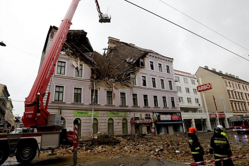 Austrian firefighters stand in front of a partially collapsed house in Vienna April 26, 2014. The house collapsed after an explosion and five residents were seriously injured, according to police. -- FILE PHOTO: REUTERS