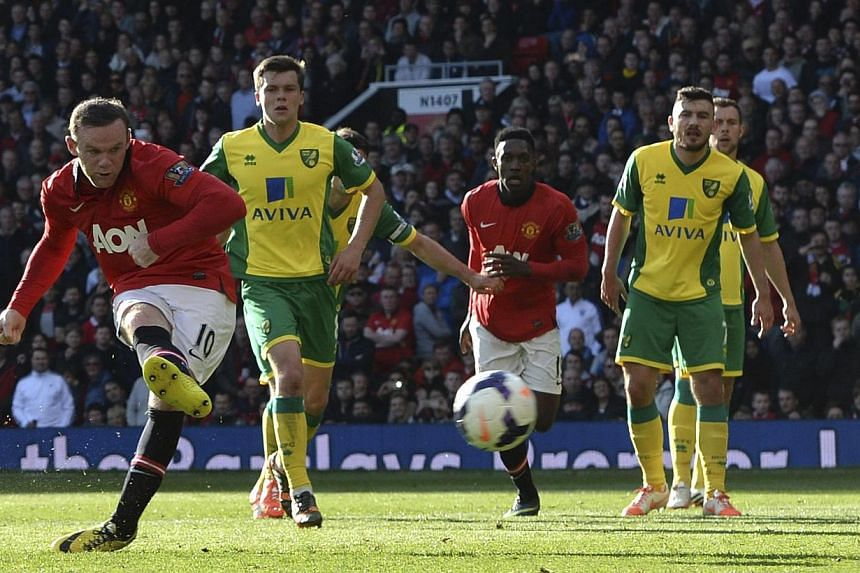 Manchester United's Wayne Rooney (left) scores a penalty against Norwich during their English Premier League match at Old Trafford in Manchester on April 26, 2014. -- PHOTO: REUTERS