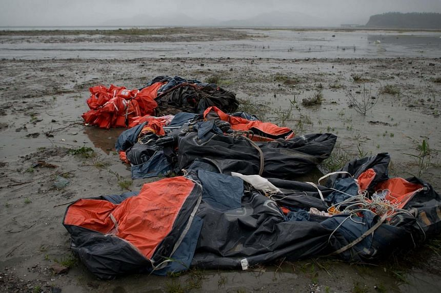 Lifeboats and life jackets recovered from the sea surrounding the 'Sewol' ferry are left at the shore near Jindo harbour where relatives of the victims are waiting for developments in the search and recovery operations on April 28, 2014.South K