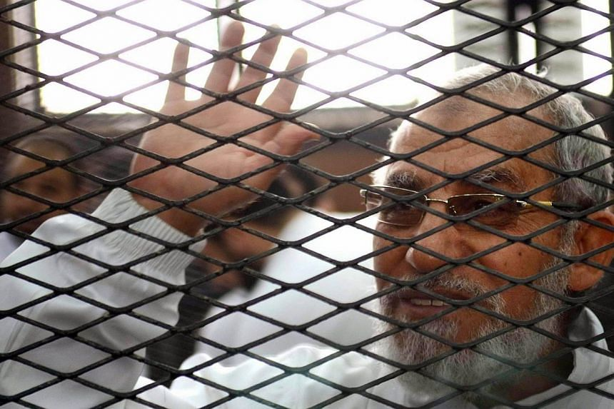 Egypt's Muslim Brotherhood's supreme guide Mohamed Badie waves from inside the defendants cage during the trial of Brotherhood members on Feb 3, 2014 in the police institute near Cairo's Turah prison.An Egyptian court on Monday, April 28, 2014,
