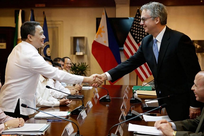 Philippine Defence Undersecretary Pio Lorenzo Batino (left) shakes hands with United States (US) Ambassador Eric John, chair of the US negotiating panel, during the seventh round of talks between the Philippines and the US on the Enhanced Defence Coo
