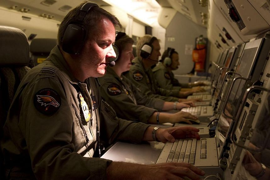 An Air Combat Officer manning the Mission Commander station aboard the RAAF E-7A Wedgetail Airborne Early Warning and Control (AEW&C) aircraft during its return from another mission in the search for the missing Malaysia Airlines Flight MH370 in