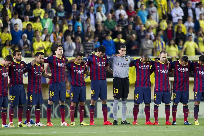 Barcelona's players hold a minute's silence for former Barcelona's coach Tito Vilanova during the Spanish league football match against Villarreal at El Madrigal stadium in Villarreal on April 27, 2014. -- PHOTO: AFP