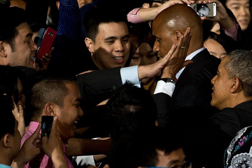 US President Barack Obama (R) high-fives a young student leaders after an interaction at the Young South-east Asian Leadership Initiative (Yseali) Town Hall during a visit to University of Malaya in Kuala Lumpur on April 27, 2014. -- PHOTO: AFP