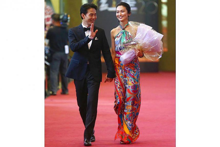 Qi Yu Wu and girlfriend Joanne Peh held hands and walked down the red carpet together. -- TNP PHOTO: GAVIN FOO