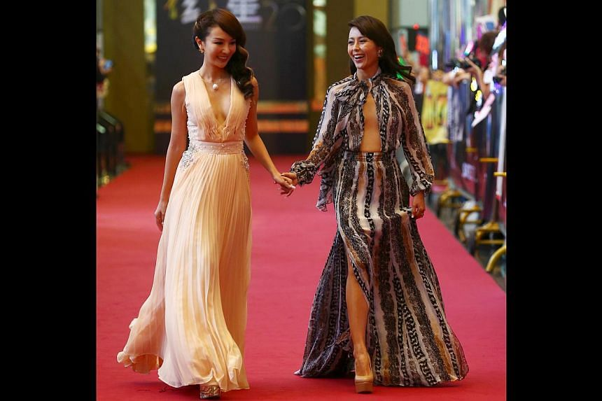 The plunging neckline, high slit and loud prints on Priscelia Chan's (right, with Chris Tong) Diane von Furstenberg dress seemed like a desperate call for attention. It was just a little too trashy for our taste. -- TNP PHOTO: GAVIN FOO