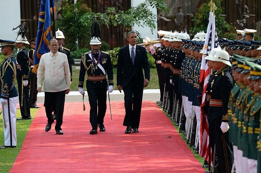 US President Barack Obama (centre right) walks with Philippine President Benigno Aquino (second from left) as they inspect an honour guard during a welcoming ceremeony at the Malacanang Palace grounds in Manila, on April 28, 2014. -- PHOTO: AFP