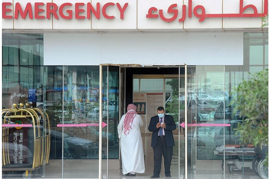A man, wearing a mouth and nose mask, checks his phone as he leaves the hospital's emergency department on April 27, 2014 in the Saudi capital Riyadh. -- PHOTO: AFP