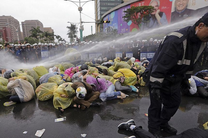 Police use a water cannon to disperse demonstrators protesting the construction of a fourth nuclear plant, in front of Taipei Railway station in Taipei on April 28, 2014.-- PHOTO: REUTERS