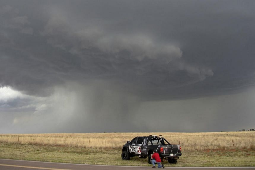 A storm chaser photographer looks at thunderstorms supercells pass through areas in Erick, Oklahoma, late on April 23, 2014. -- FILE PHOTO: REUTERS