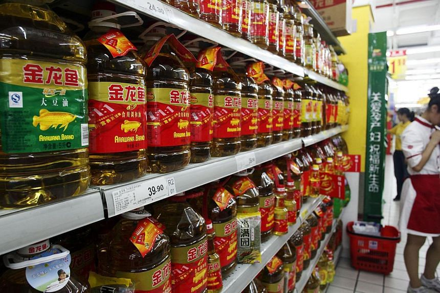 Bottles of Wilmar International Arawana brand cooking oil sit on a shelf at a supermarket in Shanghai, China. -- FILE PHOTO: BLOOMBERG