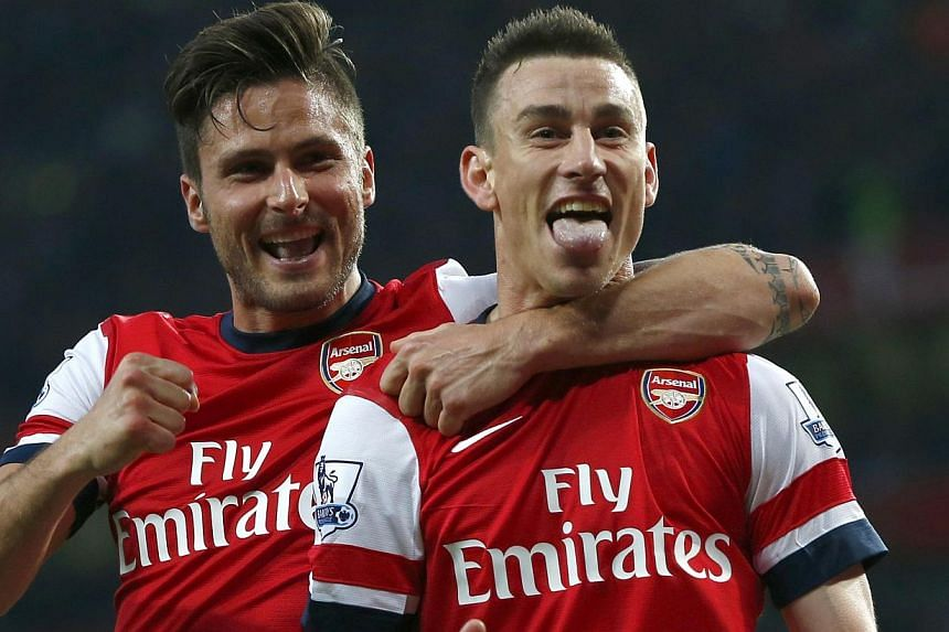 Arsenal's Laurent Koscielny (right) celebrates with team mate Olivier Giroud after scoring a goal against Newcastle United during their English Premier League soccer match at the Emirates stadium in London on April 28, 2014. -- PHOTO: REUTERS