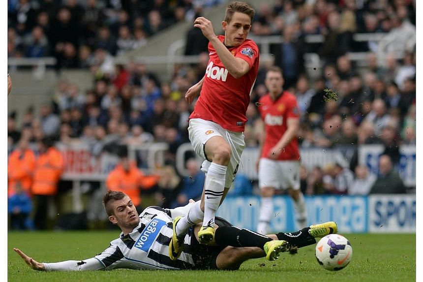Manchester United's Adnan Januzaj is challenged by Newcastle United's Davide Santon (bottom) during their English Premier League soccer match at St James' Park in Newcastle, northern England on April 5, 2014.Manchester United's teenage winger A