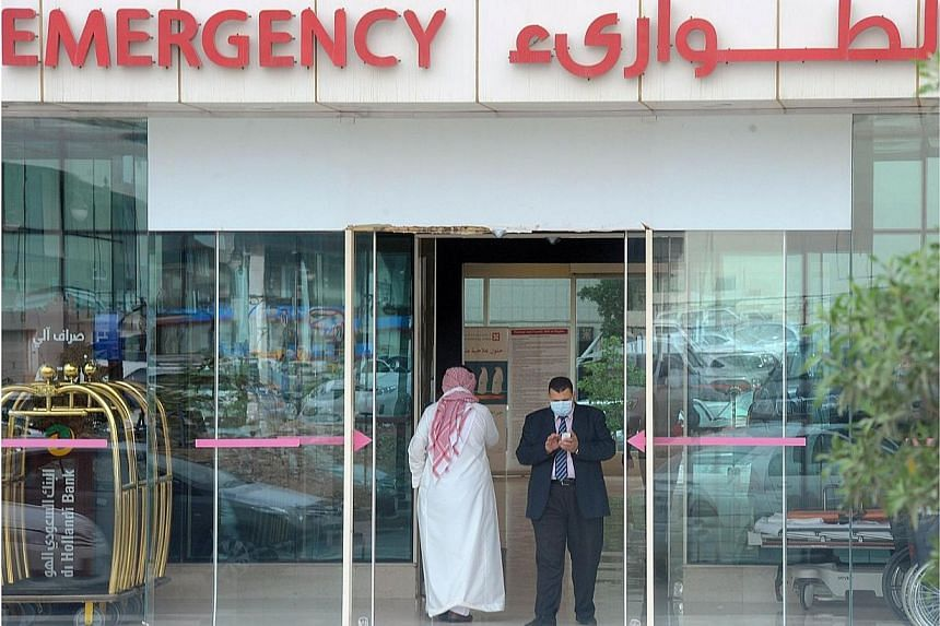 A man, wearing a mouth and nose mask, checks his phone as he leaves the hospital's emergency department on April 27, 2014, in the Saudi capital Riyadh.Over the weekend, the death toll for the Middle East Respiratory Syndrome (Mers) topped 100,