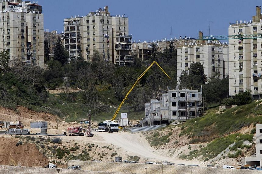 A general view taken on April 8, 2014, shows Israeli construction cranes and excavators at a building site of new housing units in the Jewish settlement of Neve Yaakov, in the northern area of east Jerusalem.Israel approved plans for nearly 14,