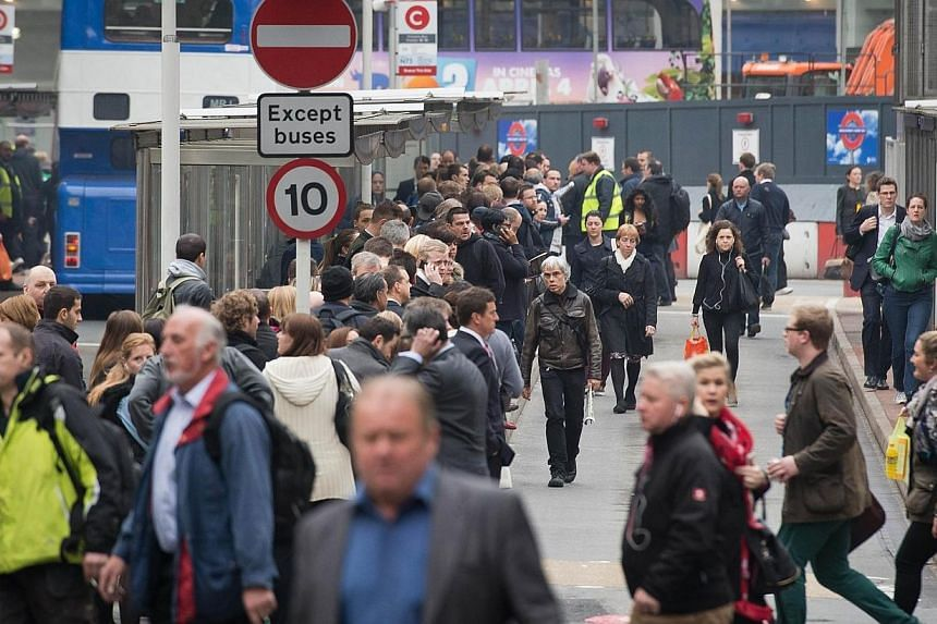 Commuters form long queues as they wait for buses outside Victoria station in London, on April 29, 2014, as a planned 48 hour underground train strike came into effect late Monday night, April 28, 2014, night. -- PHOTO: AFP