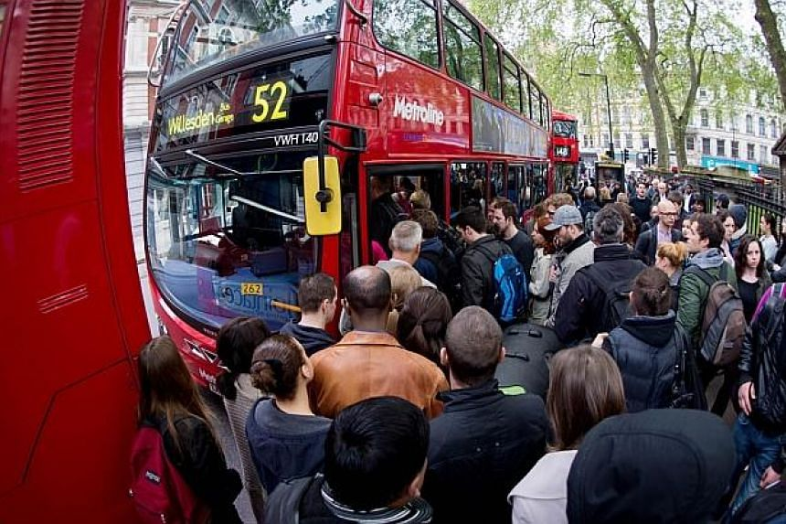 Commuters jostle for access to buses near Victoria station in London, on April 29, 2014, as a planned 48 hour underground train strike came into effect late Monday night, April 28, 2014, night. -- PHOTO: AFP