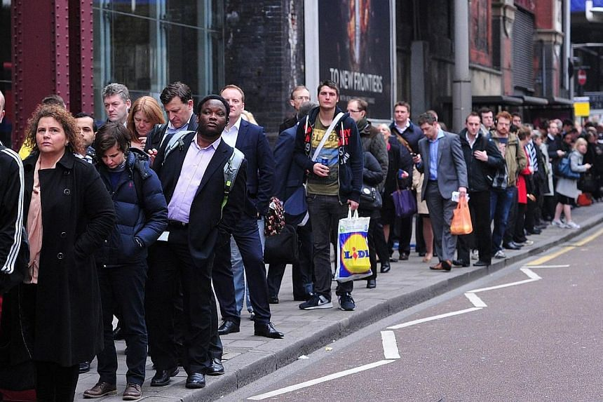 Commuters form long queues for buses outside Waterloo Station in London on April 29, 2014, as a planned 48 hour underground train strike came into effect late Monday, April 28, 2014, night.Millions of commuters struggled to reach work on Tuesda