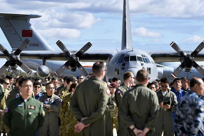 International and Australian air crews involved in the search for missing Malaysia Airlines plane MH370, prepare for an official photograph on the tarmac at the Royal Australian Air Force (RAAF) Pierce Base in Bullsbrook, near Perth on April 29, 2014
