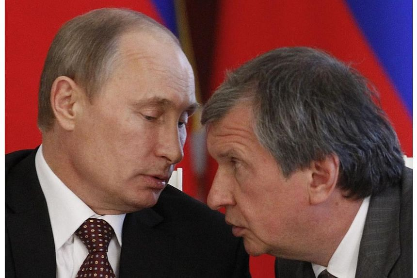 OAORosneft President and Chairman of the Management Board Igor Sechin (right) speaking with Russia's President Vladimir Putin (left) during a signing ceremony with his Venezuelan counterpart Nicolas Maduro at the Kremlin in Moscow on July 2, 20