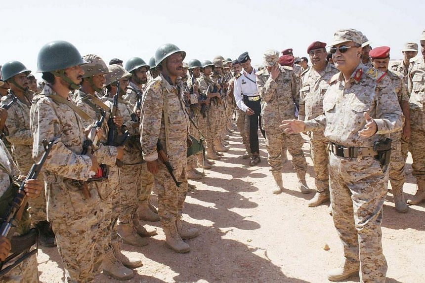 Yemen's Defence Minister Major General Muhammad Nasir Ahmad (right) talks to troops as he tours an army barrack in the southeastern province of Shabwa on April 28, 2014. Yemeni troops, backed by air force planes, launched a major offensive against Al