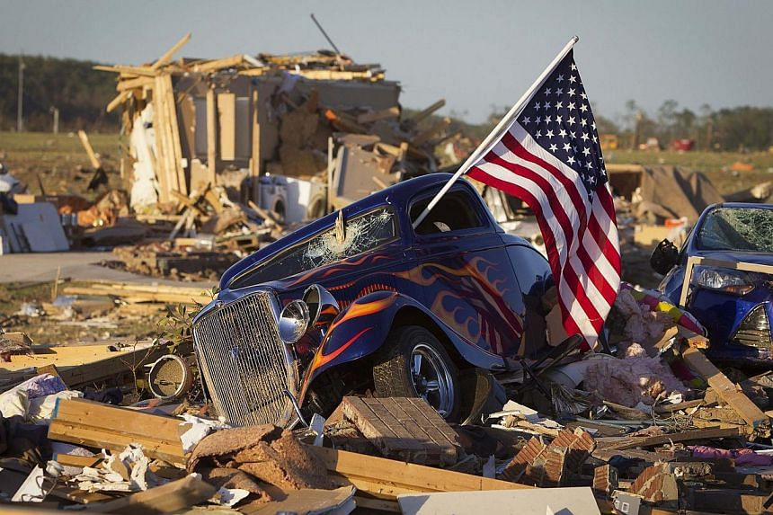 A US flag sticks out the window of a damaged hot rod car in a suburban area after a tornado near Vilonia, Arkansas on April 28, 2014. -- PHOTO: REUTERS