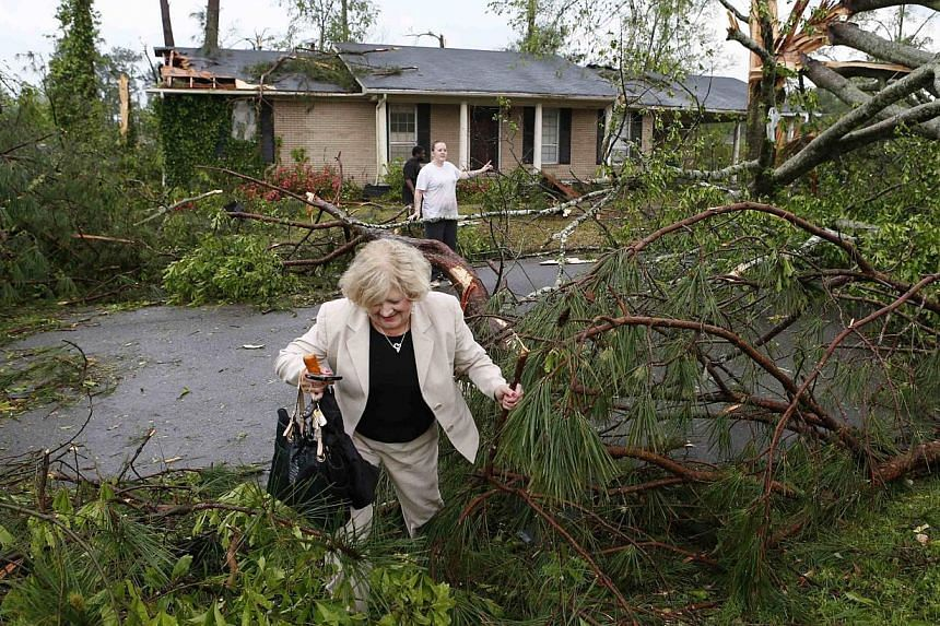Cathy Norman tries to climb through debris and get to her house on Marquette Street in Tupelo, Mississippi on April 28, 2014. -- PHOTO: REUTERS