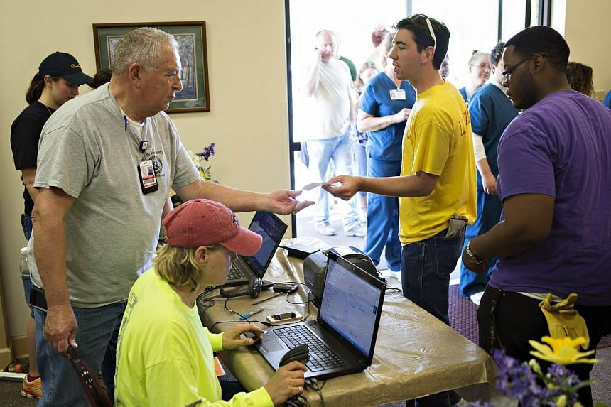 Ken Brown hands out IDs at Beryl Baptist Church to volunteers after a tornado yesterday tore through the area for the second time in three years, on April 28, 2014 in Vilonia, Arkansas. After deadly tornadoes ripped through the region, leaving more t