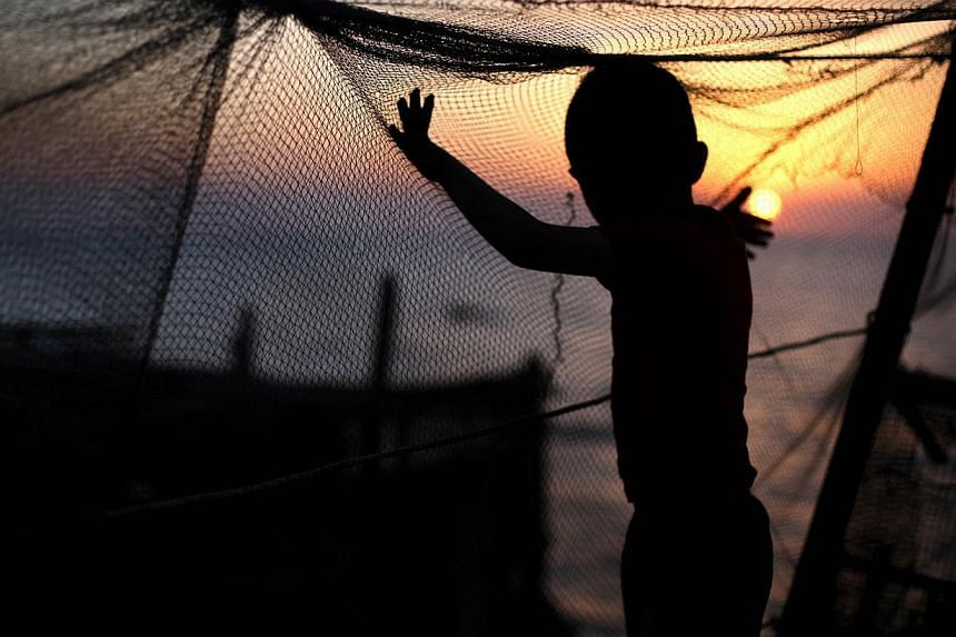 A Palestinian child plays with a fishing net as the sun sets over Gaza City on April 28, 2014. -- PHOTO: AFP