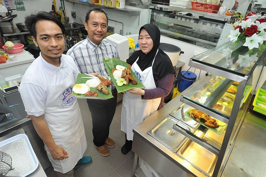 Master trainer Sulaiman Abu (centre), 52, with trainees Noor Marina Salleh, 37, and Mohamad Zulfadhil, 25, and the nasi lemak they have learnt to prepare.