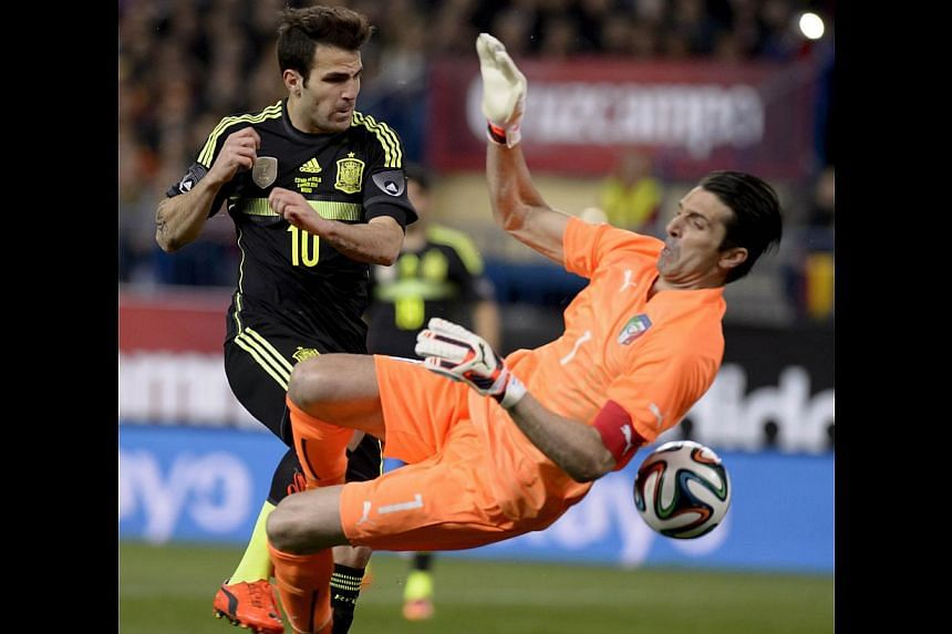 Spanish midfielder Cesc Fabregas (left) vying with Italy's goalkeeper Gianluigi Buffon during a 2014 World Cup friendly last month. The spiralling prices that viewers in Singapore pay for sports programmes, particularly the upcoming World Cup, sugg