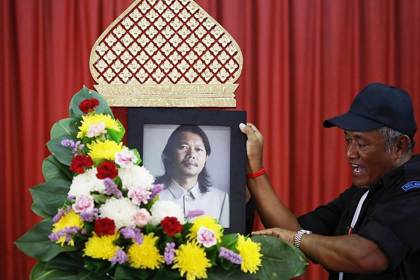 A man holding a portrait of poet Kamol Duangphasuk at a Buddhist temple in Bangkok last week. The activist was shot dead last Wednesday. -- PHOTO: REUTERS