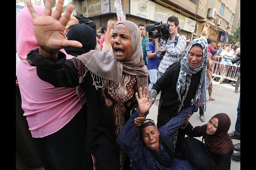 Egyptians reacting outside a court during the trial of supporters of toppled president Mohamed Mursi in Minya yesterday. The judge is expected to confirm the latest batch of death sentences on June 21.