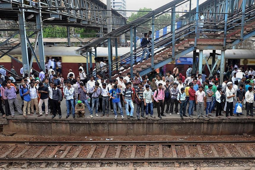 In this photograph taken on April 7, 2014, Indian commuters crowd onto a platform as they wait for a train at a station on the suburban train network in Mumbai. -- FILE PHOTO: AFP